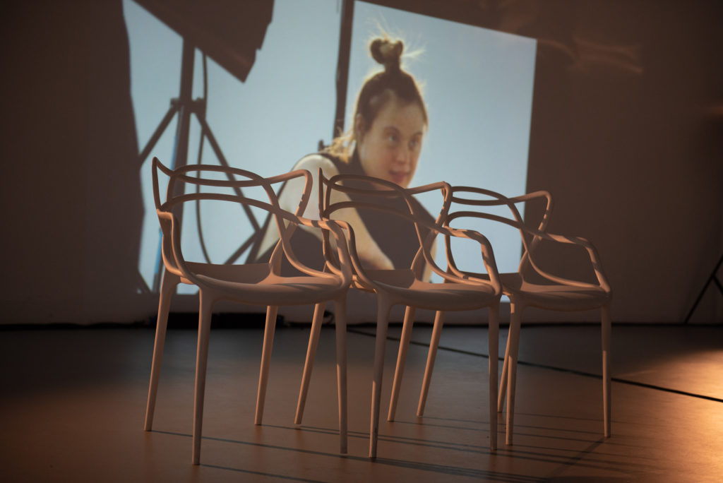 Three chairs at the front of a stage sit before a video projection showing a learning disabled female performer
