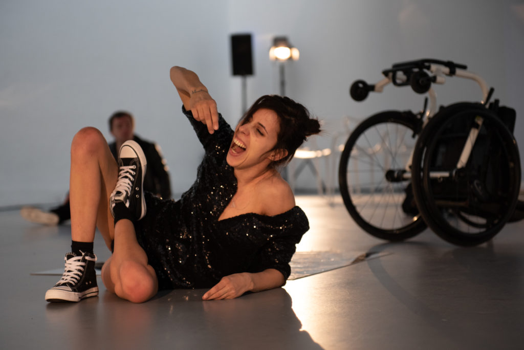 A brunette woman screams on the floor, her wheelchair beside her. She wears Converse trainers and a sparkly black dress.