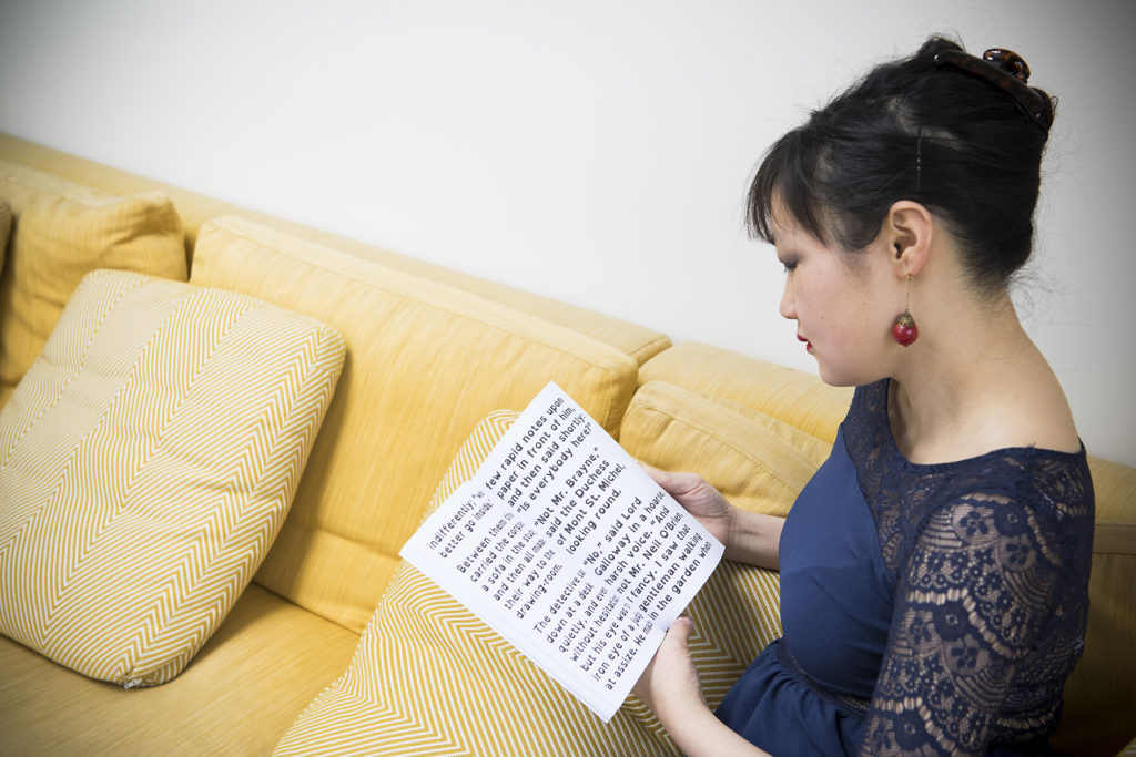 East Asian woman relaxing on sofa reading large print book