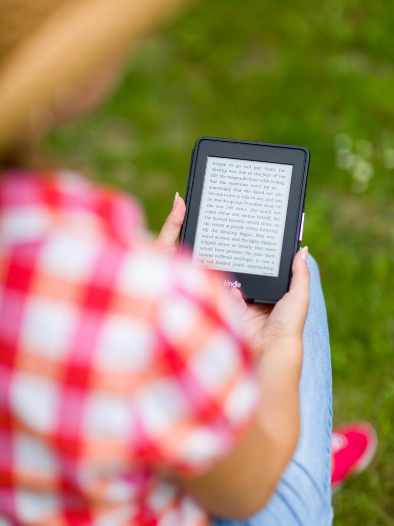 Photo of a person sitting outside holding an e-book reader. The person is out of focus and facing away from the camera, wearing a plaid shirt. The Kindle they hold displays an e-book, and is in sharp focus.