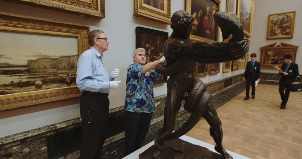 Two white men, one is giving the other a guided touch tour of a bronze statue of a man wrestling a python