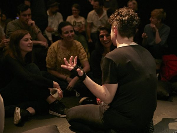 Photograph of Jess Thom, a white woman with curly brown hair sitting on the floor, shot from behind, she is talking to a large audience gathered very close to her