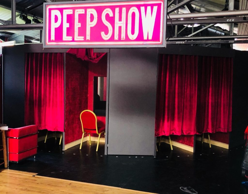 Huge neon pink writing displays the words  'Peep Show'. Underneath sits a red chair facing a hole in the wall and red velvet curtains either side.