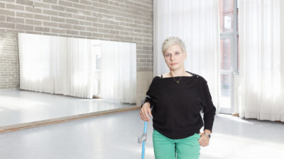 A woman with short cropped light blonde hair stands in a dance studio with a crutch. She is wearing a black top and mint green trousers.
