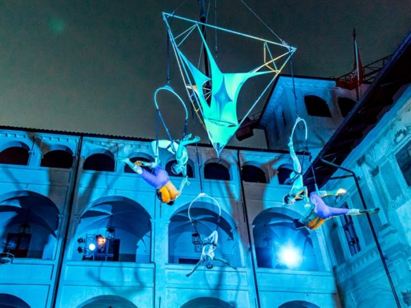 Blue light illuminates an aerial performance suspending performers high in the air in a historic courtyard.