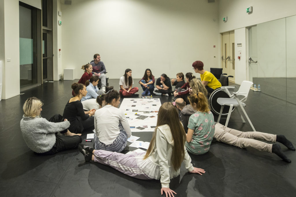 A mixed group of participants sit on the floor in a circle, gathered around a large sheet of paper with images and collage.