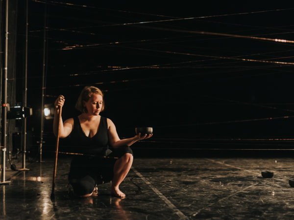 Woman with red hair and a walking stick is kneeling on a black floor in a dark theatre space holding a bowl