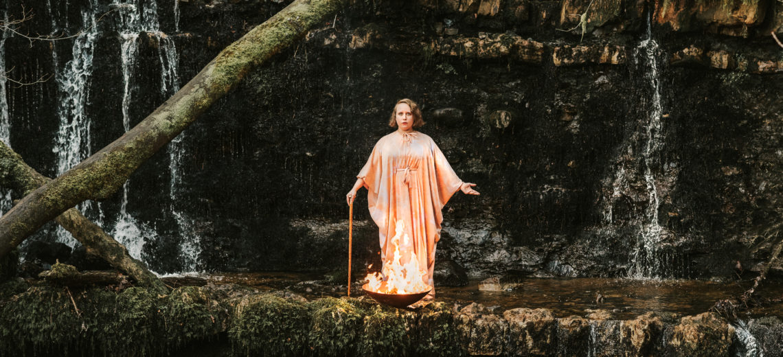 A woman in pink robes stands on the ledge of a small waterfall with a bowl of fire at her feet