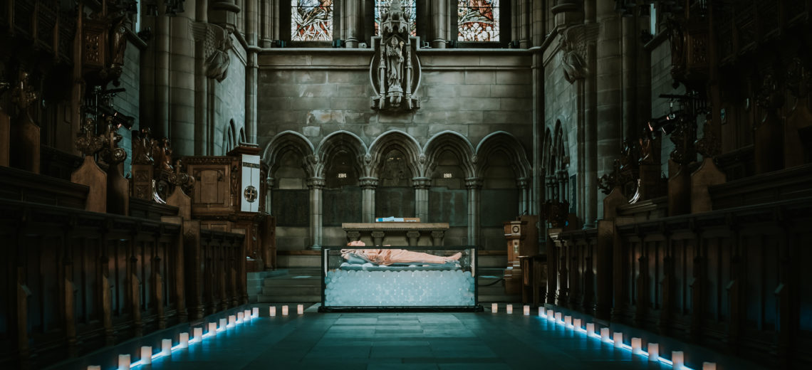 At the altar of a church a woman lies on an open tank of ice