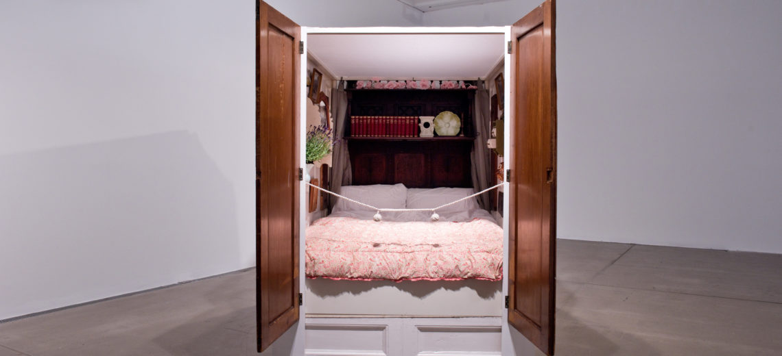 A bed entirely enclosed by panels, filled with old things