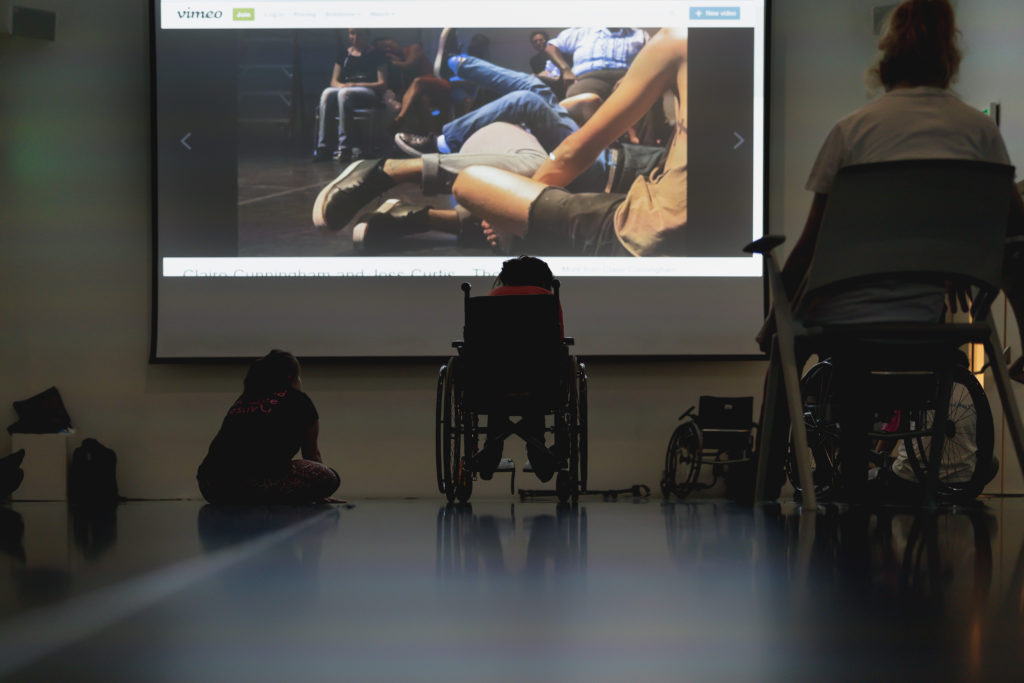 Two wheelchair users and another participants sit viewing a large screen video of a dance performance.