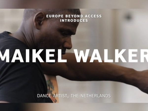 A black male performer dances in a studio, his arm stretched forward across the screen
