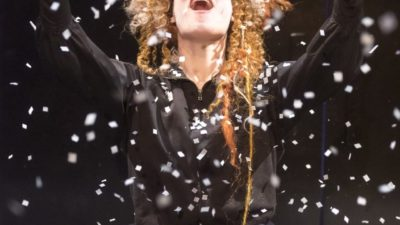 Female performer looks joyously to the sky as snowflakes fall around her She is wearing a big blonde wig and a black dress