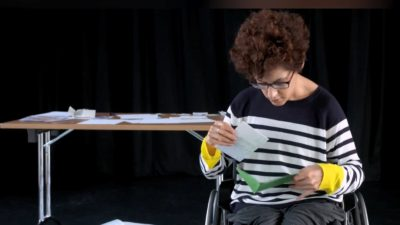 A female performer in a wheelchair sifts through an abundance of letters
