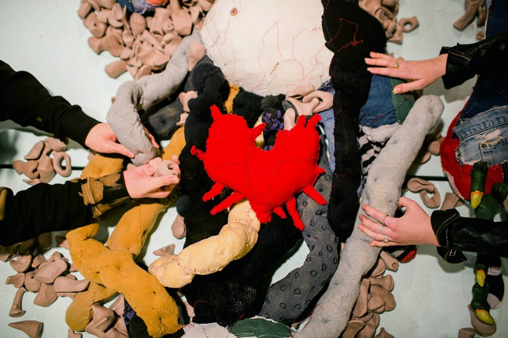 Two people reach out to touch Big Softie, a bulbous 12 foot soft sculpture monster, composed of soft and dimpled guts made from stuffed knee socks and nylon stockings, and examine the Unidentified Remains that are scattered amongst them. At the centre of it all lies Big Softie's heart, a red patchwork soft sculpture with tendrils extending outward.