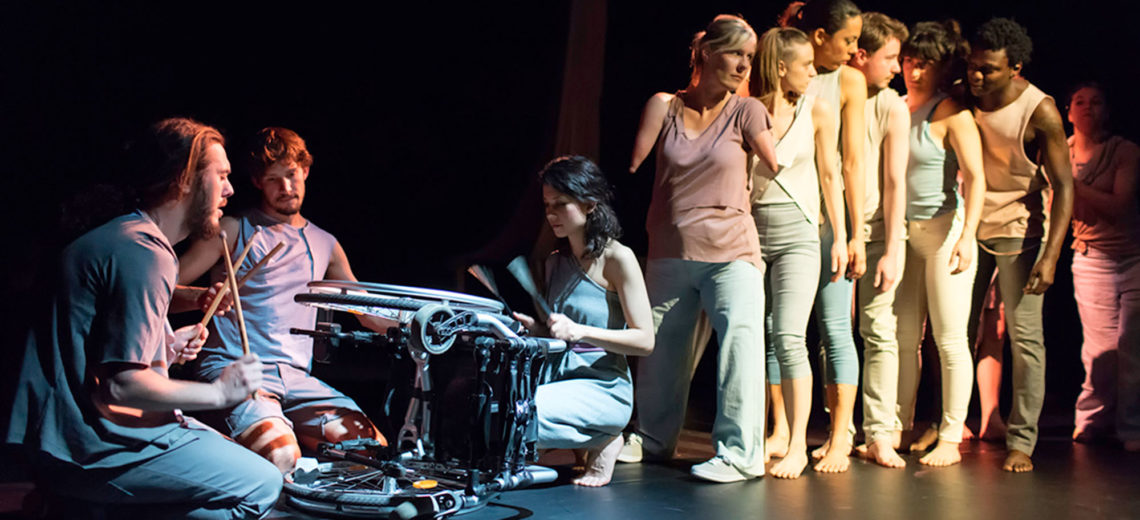 Performers stand in a line towards an overturned wheelchair on which three other seated performers play with percussion sticks.