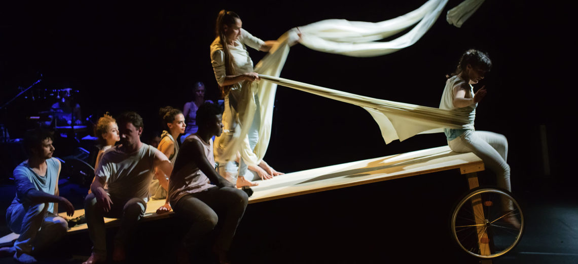 On the top edge of a sloping wheeled table, a performer is tied by a long white cloth and pulled back by another performer who's grabbing the cloth like a horse-driver.