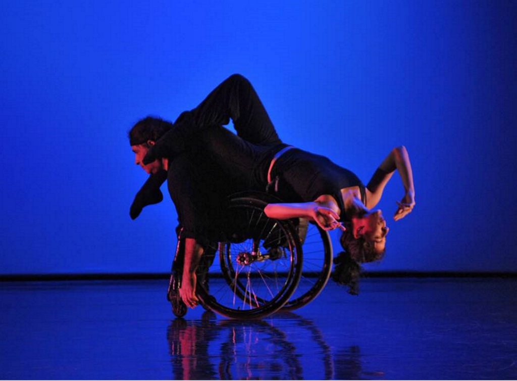White female dancer balances upside down on the back of a white male dancer who uses a wheelchair