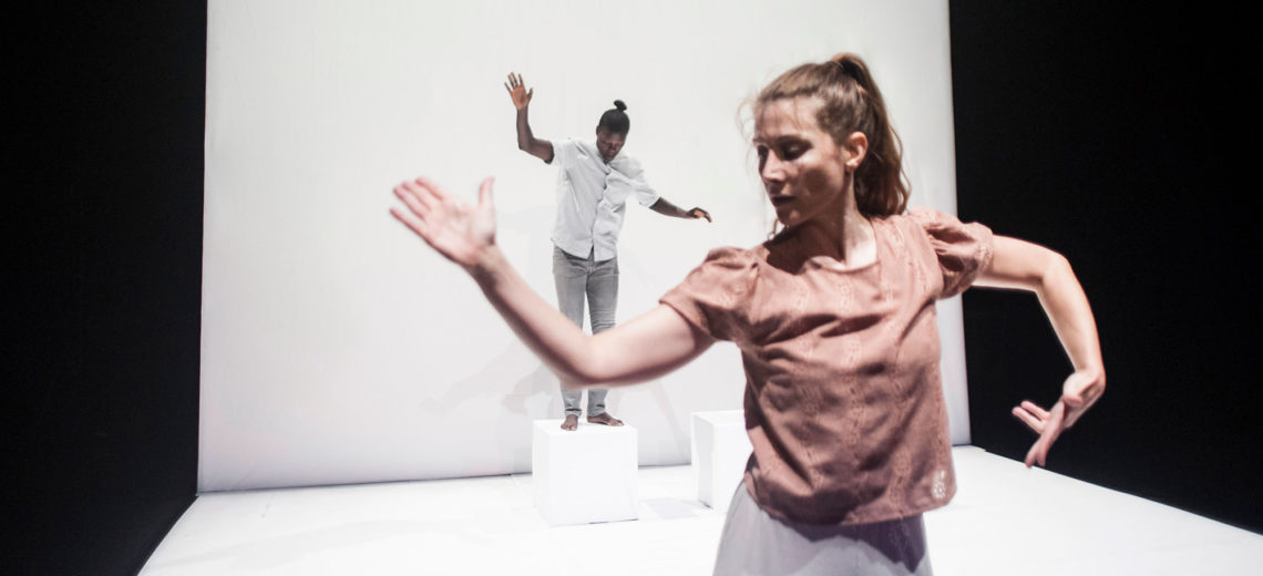 On a white spotless stage, two dancers open their hands like if trying to find their balance, one in the very front of the stage and one in the back on a white cube.