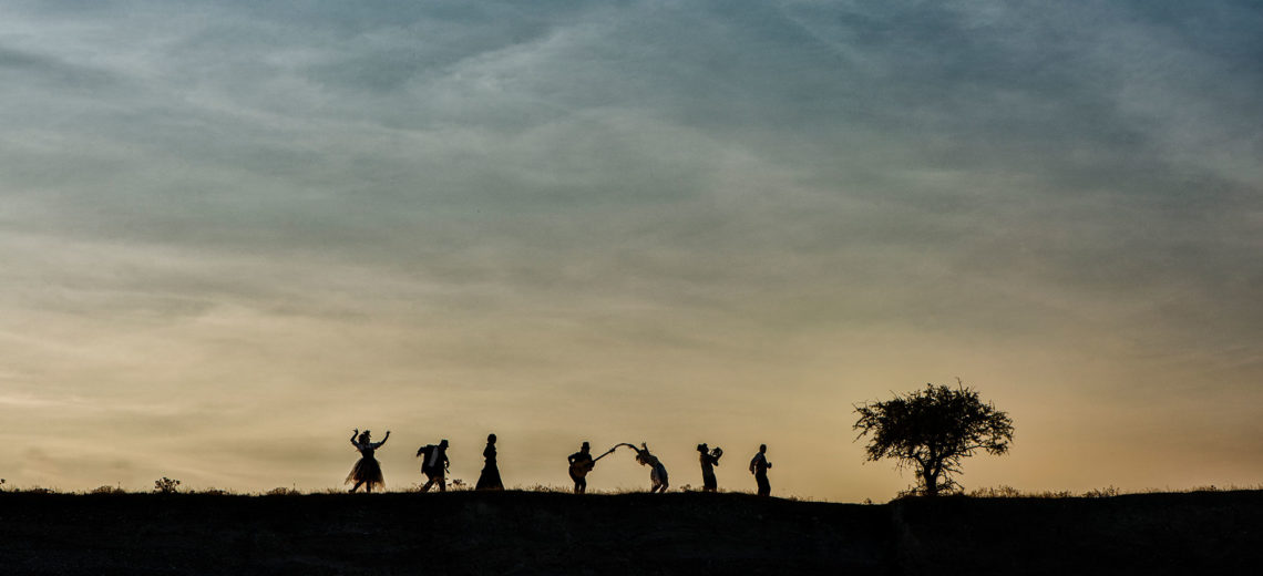 7 dark strangely shaped human silhouettes walk on the top of a dark hill towards a tree in front of a cloudy colourful sky.