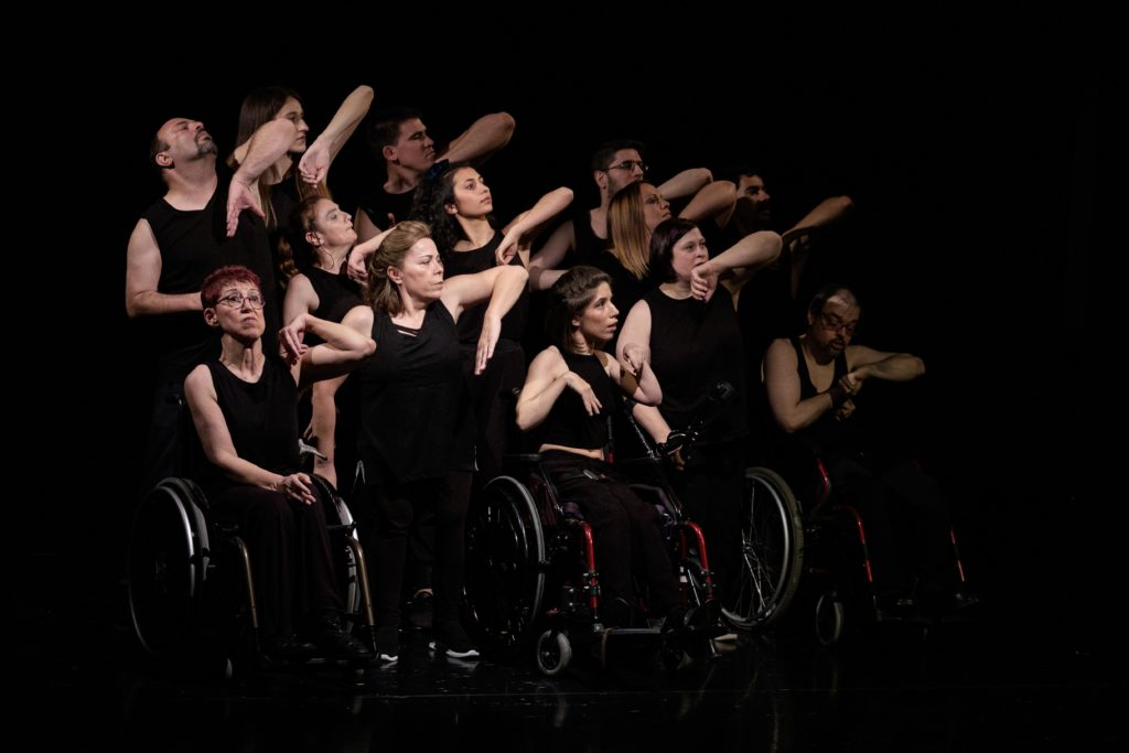 Ensemble of white disabled and non-disabled dancers all dressed in black, they are raising their left elbows in unison.