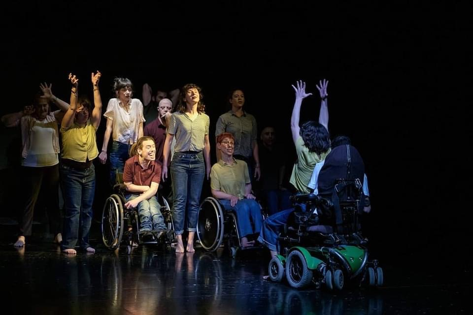 Wheelchair using white woman raising her hands in the air as she faces a mixed group of disabled and non-disabled white people who are straining upwards in response.