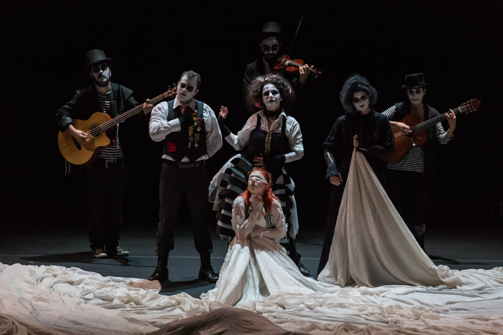 6 performers in black and white face paint play instruments whilst another in the centre of them is blindfolded, wearing a dress with a massive train which is bunched up around them all.