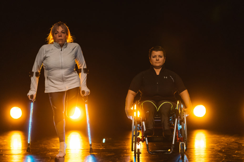 Two white female dancers on stage. One is in a wheelchair and the other is using illuminated crutches. They are brightly backlit.