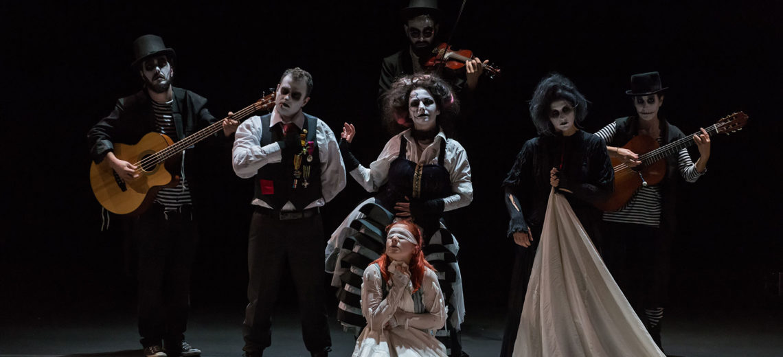 On a blackbox stage, 6 performers with white painted faces and black eyes, dressed in old-used aristocratic costumes and caring instruments are looking towards us, whilst another in the centre of them is blindfolded.