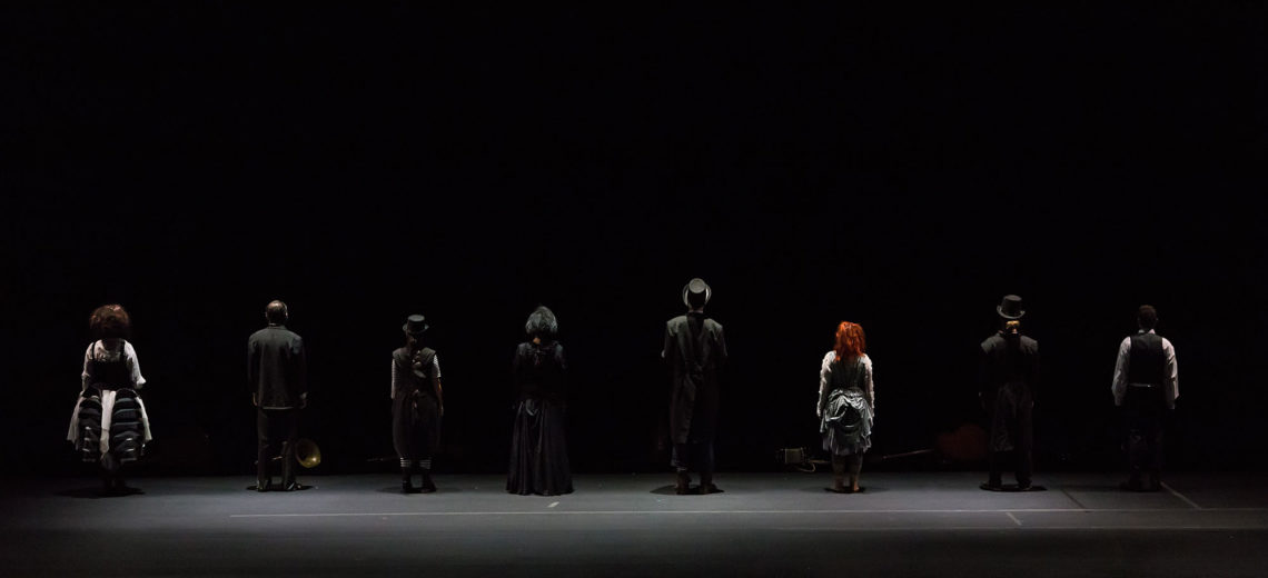 8 performers stand in line at the end of a black stage with their back towards us, dressed in black old fashion used aristocratic costumes and top hats.