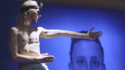A white man with a camera strapped to his head stands in front of a blue background that has a man's face projected onto it.