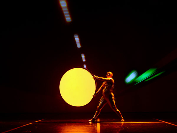 A learning disabled man ina silver body suit holds a glowing yellow circle on a stage