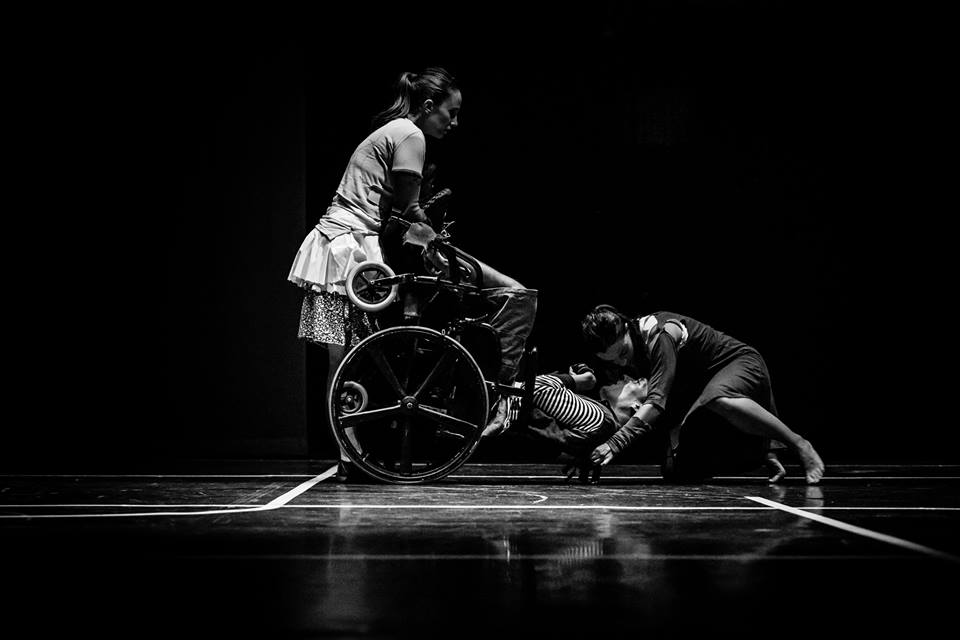 A wheelchair user is balanced on their wheels whilst two other performers hold their head and feet respectively.