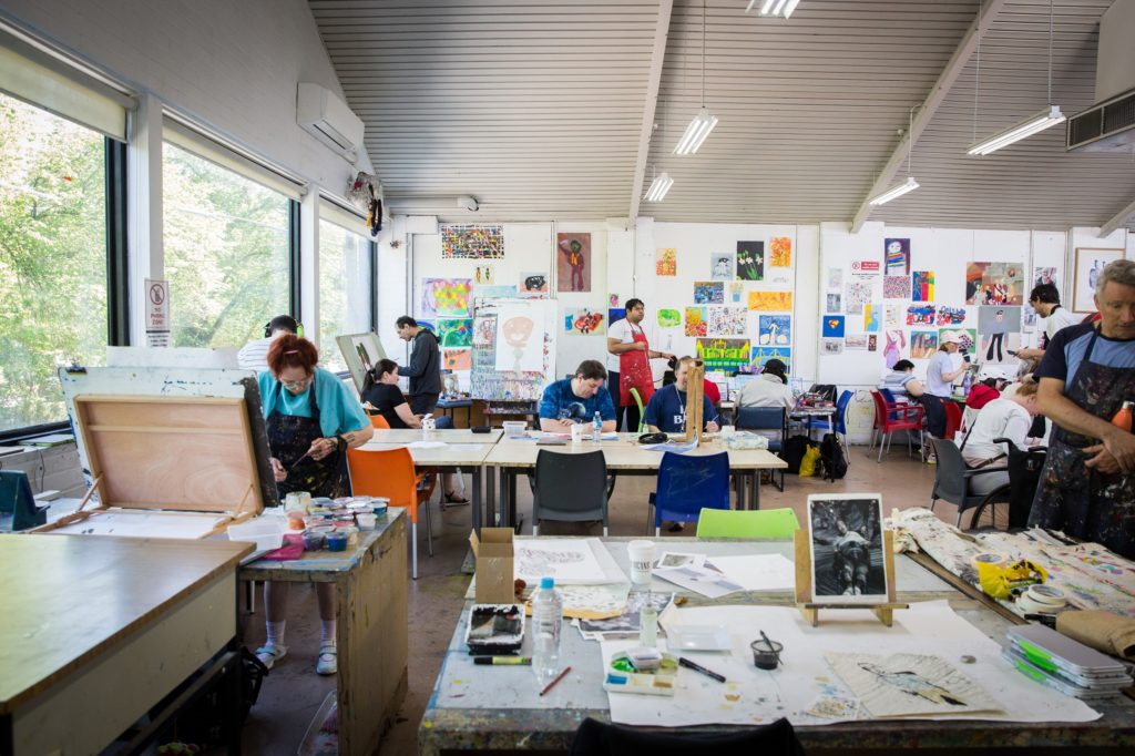 A messy, light-filled joint studio working space with various learning disabled artists working on different projects