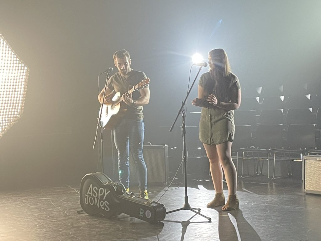 A white female singer with a white male guitarist stand on stage performing