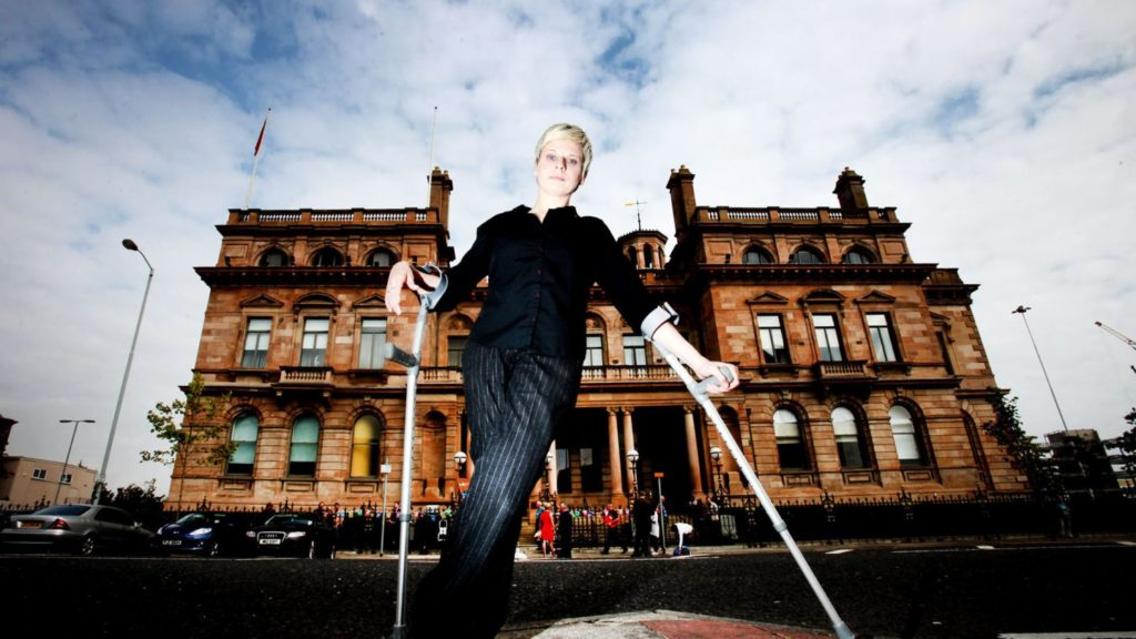 A white woman with crutches stands in front of a grand Victorian building
