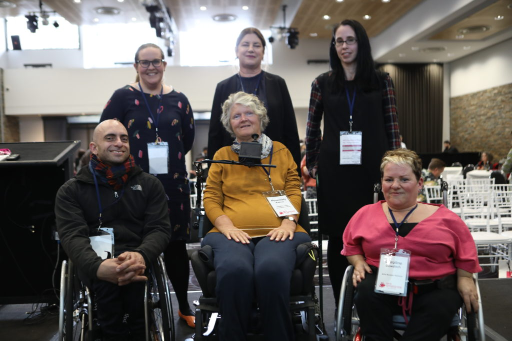 6 disabled people, three in wheelchairs smile for the camera, each with large name tags around their necks
