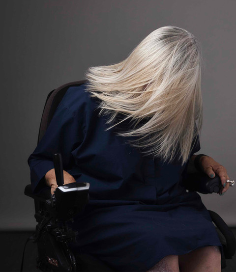 Female wheelchair user with flowing blonde hair swishes it so that it covers her face