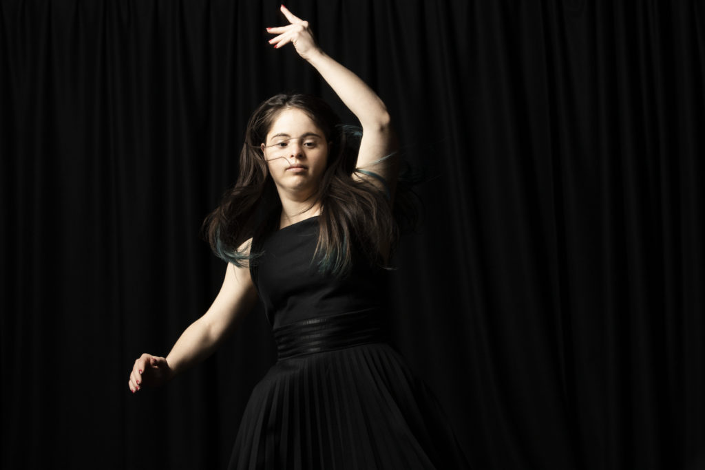 White learning disabled woman in a black dress dances expressively
