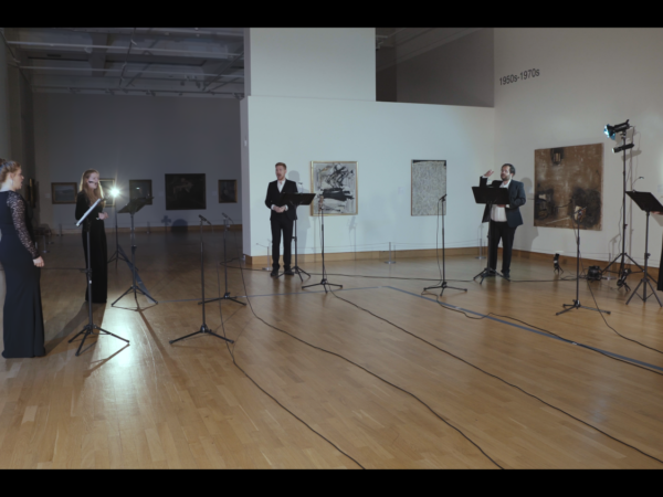 5 white classical singers in black attire perform in a gallery setting