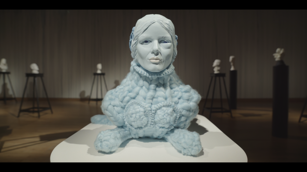 Photograph of a creature with lions body made of blue wool, it's head is realistic sculpture of a woman's head