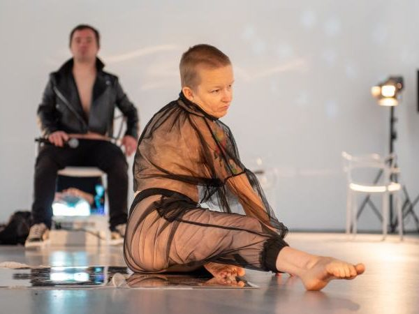 A woman with a shaved head, clothed in a meshed semi-transparent outfit stretches one leg across the floor.