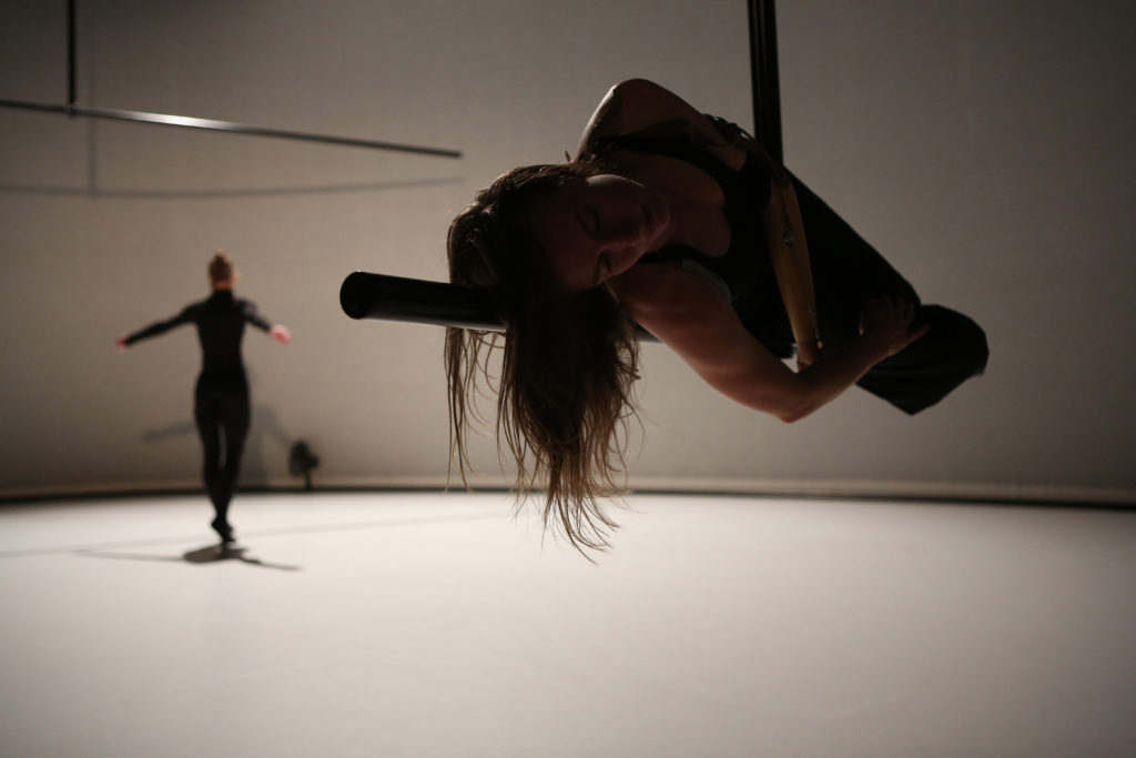 A white female dancer with a prosthetic arm balances on a floating L-shaped pole, while another dancer dressed in black performs in the background.