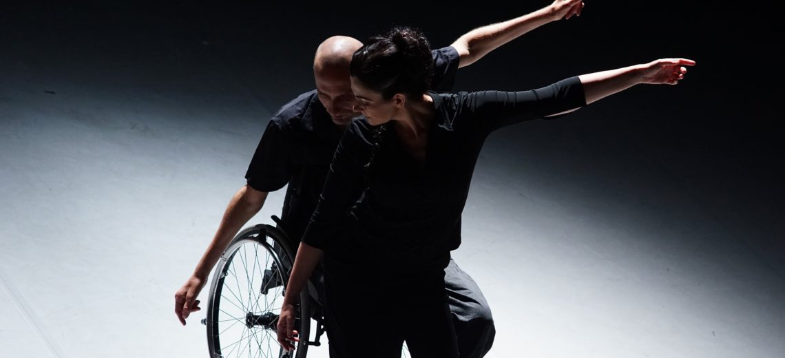 Women dancer in front of and supported by Male wheelchair dancer, both their left hands are reaching out to the side