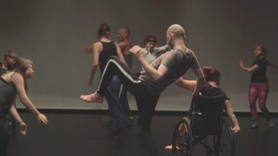 A group of dancers, some with wheelchairs, move energetically around a space, twisting, rotating, with vibrance.