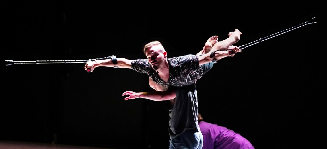 Male dancer holding crutches lying on the shoulders of another male dancer on a stage