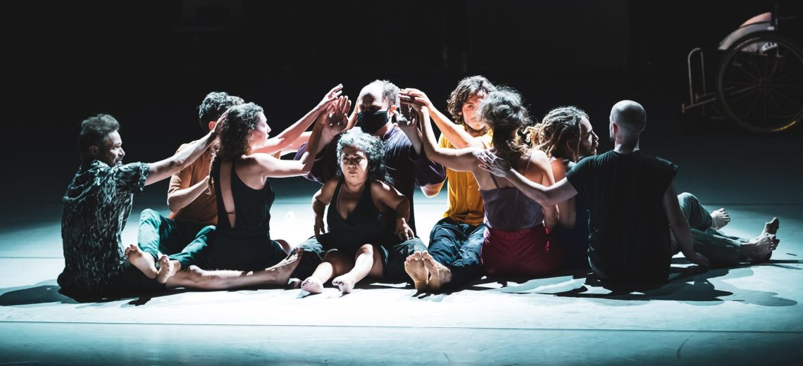 Nine dancers sitting on a stage reaching out with their hands towards the central person.
