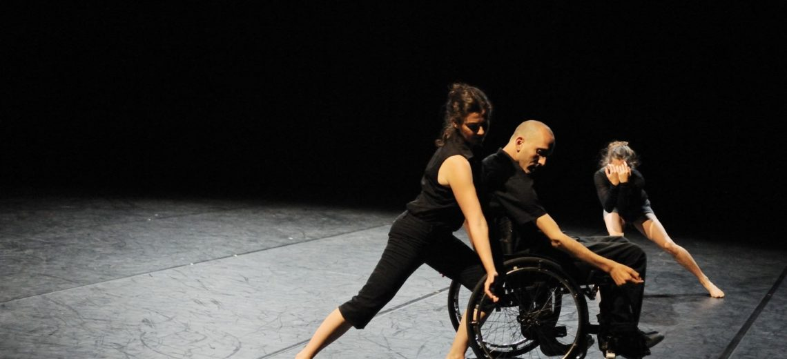3 dancers on stage wearing black. Woman dancer stand next to a male wheelchair dancer, both their right hands outstretched forward. In the background the third dancer covers her face with her hands.