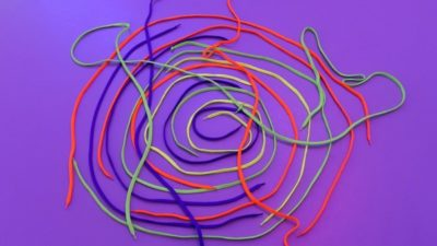 A bright purple graphic with swiggly lines in red, yellow, blue and green. These lines appear to be made with shoelaces.