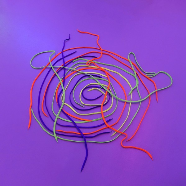 A bright purple graphic with swiggly lines in red, blue, yellow and green. These lines appear to be made with shoelaces.